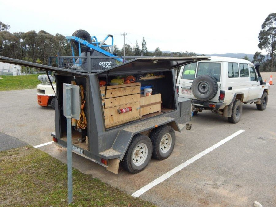 Landmate white 4WD vehicle and trailer with tools and gear.