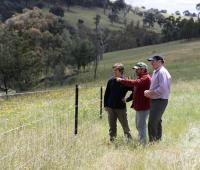 Landmate coordinator and two Greta Valley Landcare members standing next to a fence in a paddock.